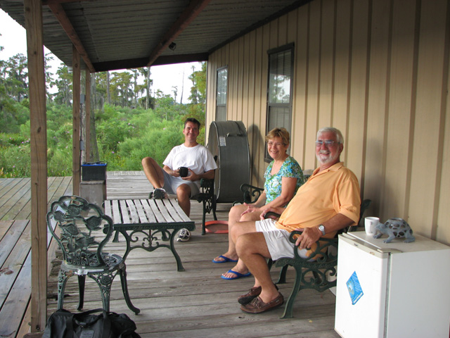 Mom, Dad and Conrad on porch at swamp house.