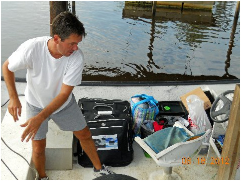 Conrad tossing bags onto pier at the swamp house.